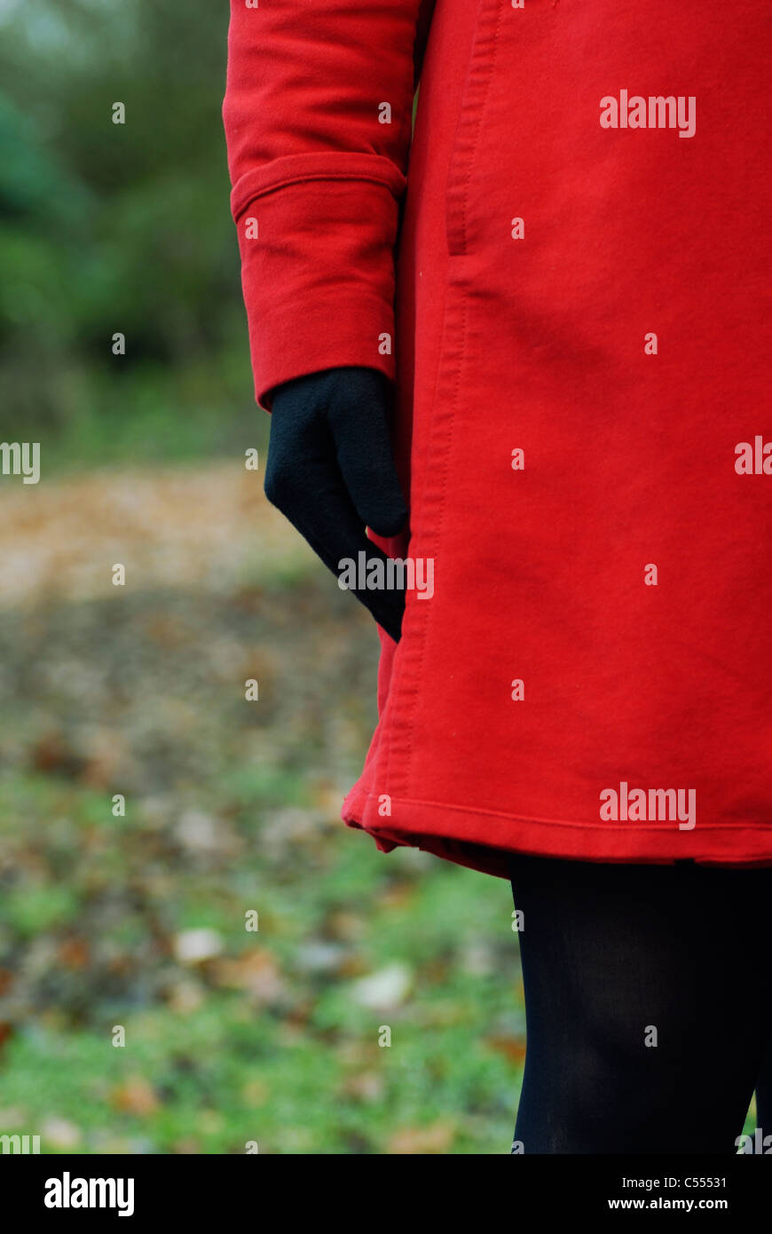 Woman in red coat and gloves standing outdoors - Stock Image