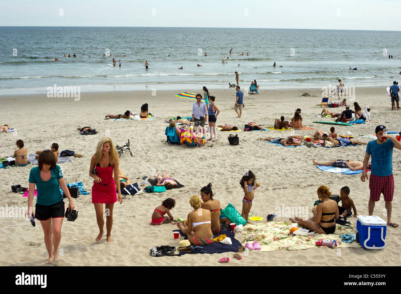 Beachgoers take advantage of the warm summer sun at Rockaway Beach in the Queens borough of New York Stock Photo