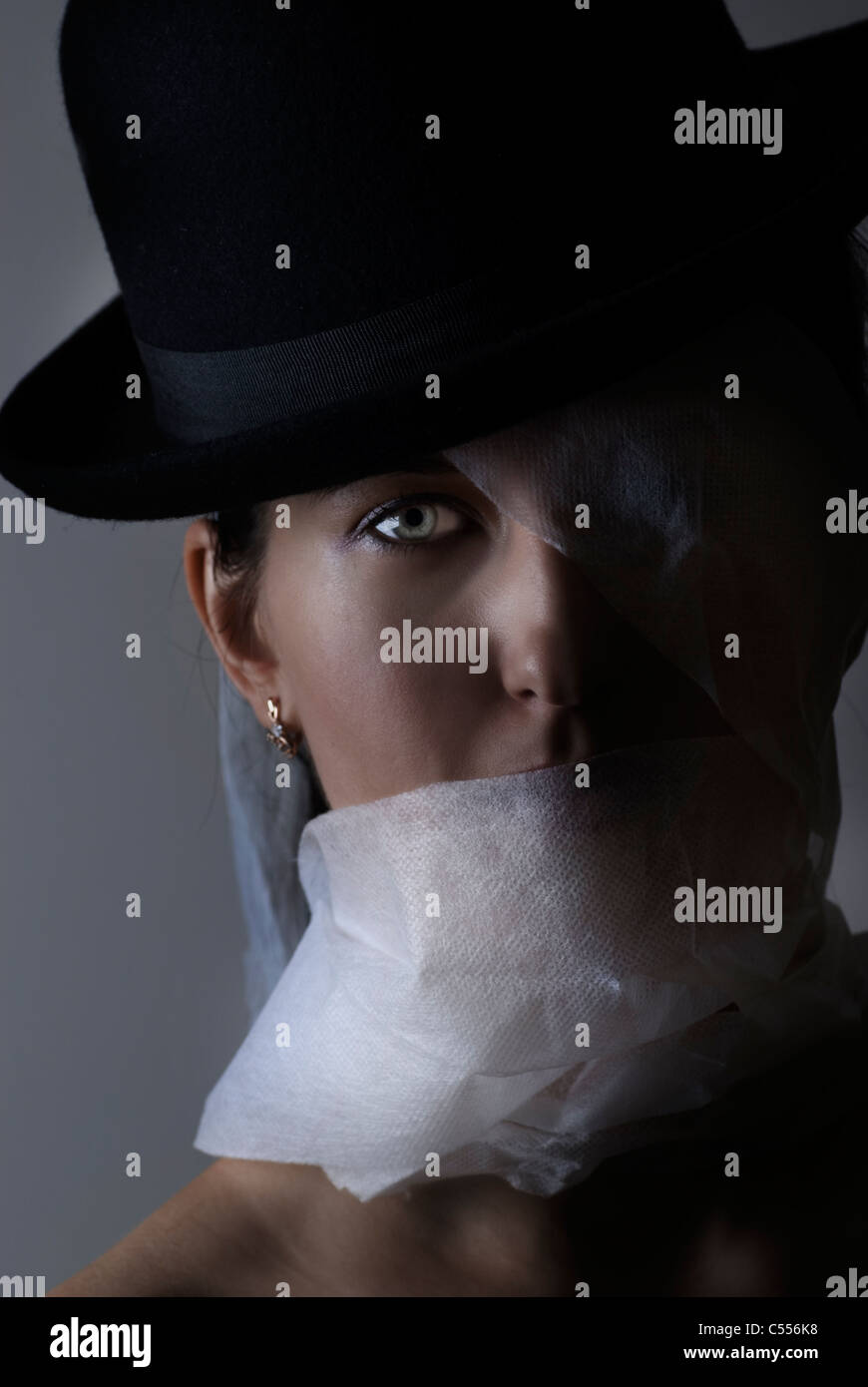 Woman wrapped in bandage wearing a bowler hat - Stock Image