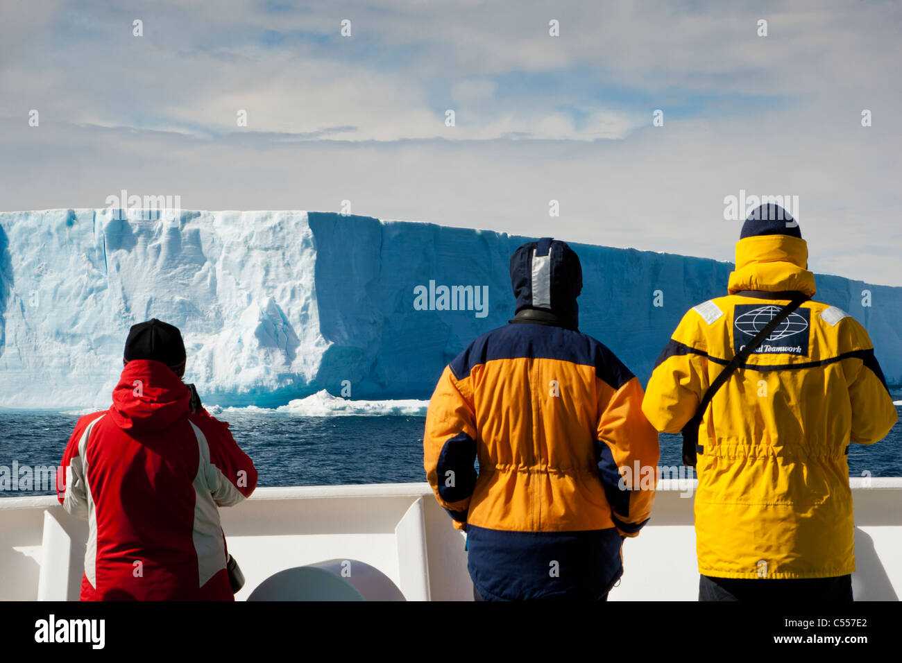 Closeup 3 Antarctic expedition cruise passengers on outside ships deck watch as giant blue iceberg floats by in Stock Photo