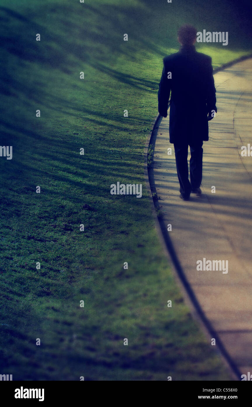 Mysterious male figure walking away - Stock Image