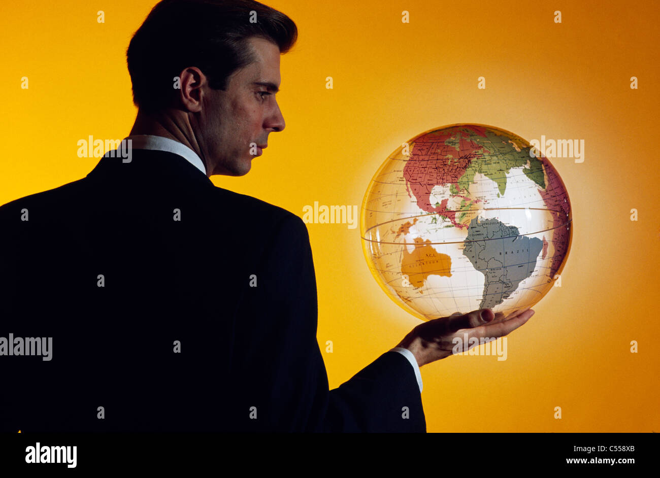 Businessman holding a globe Stock Photo