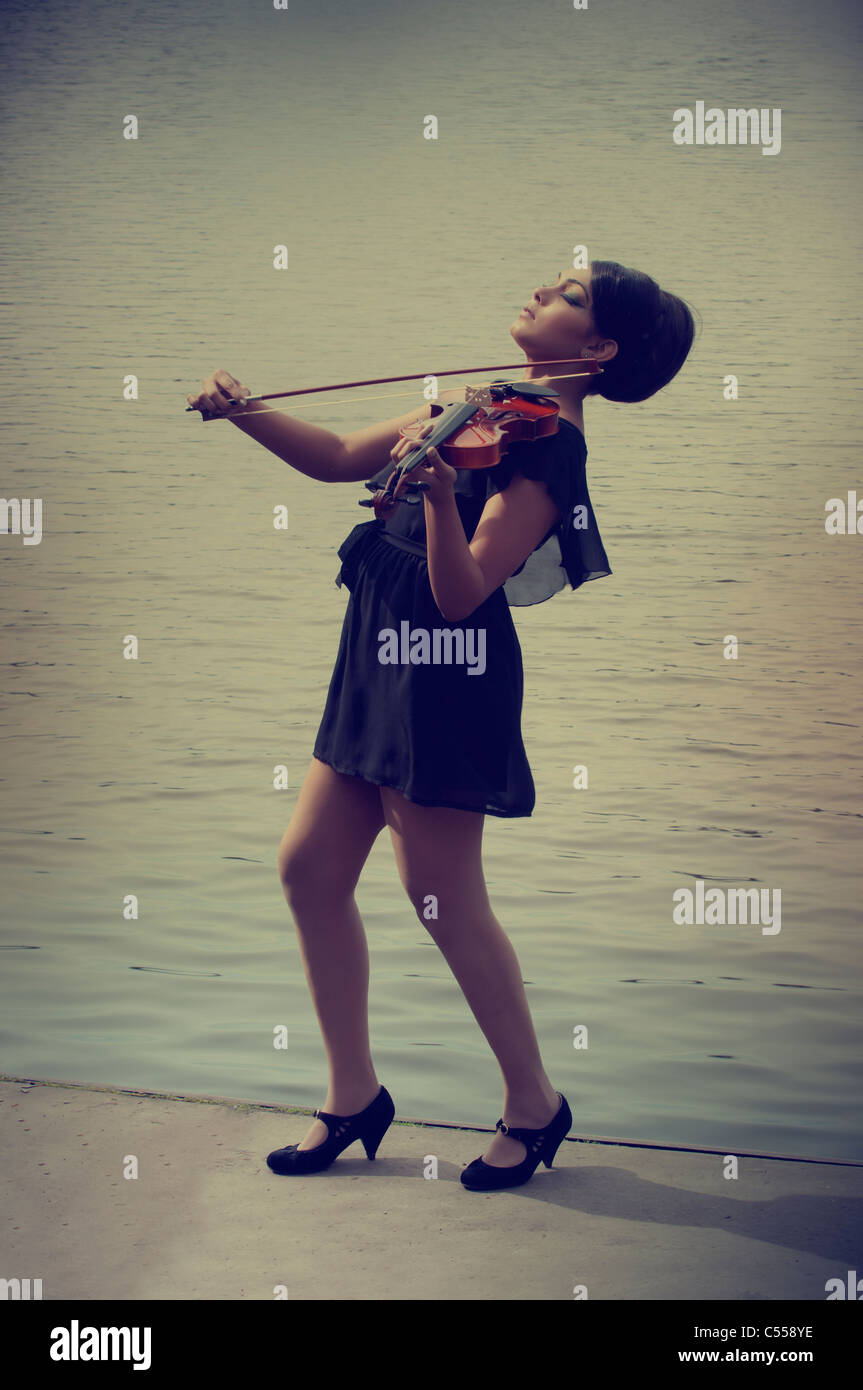 Woman standing by the lake playing violin - Stock Image
