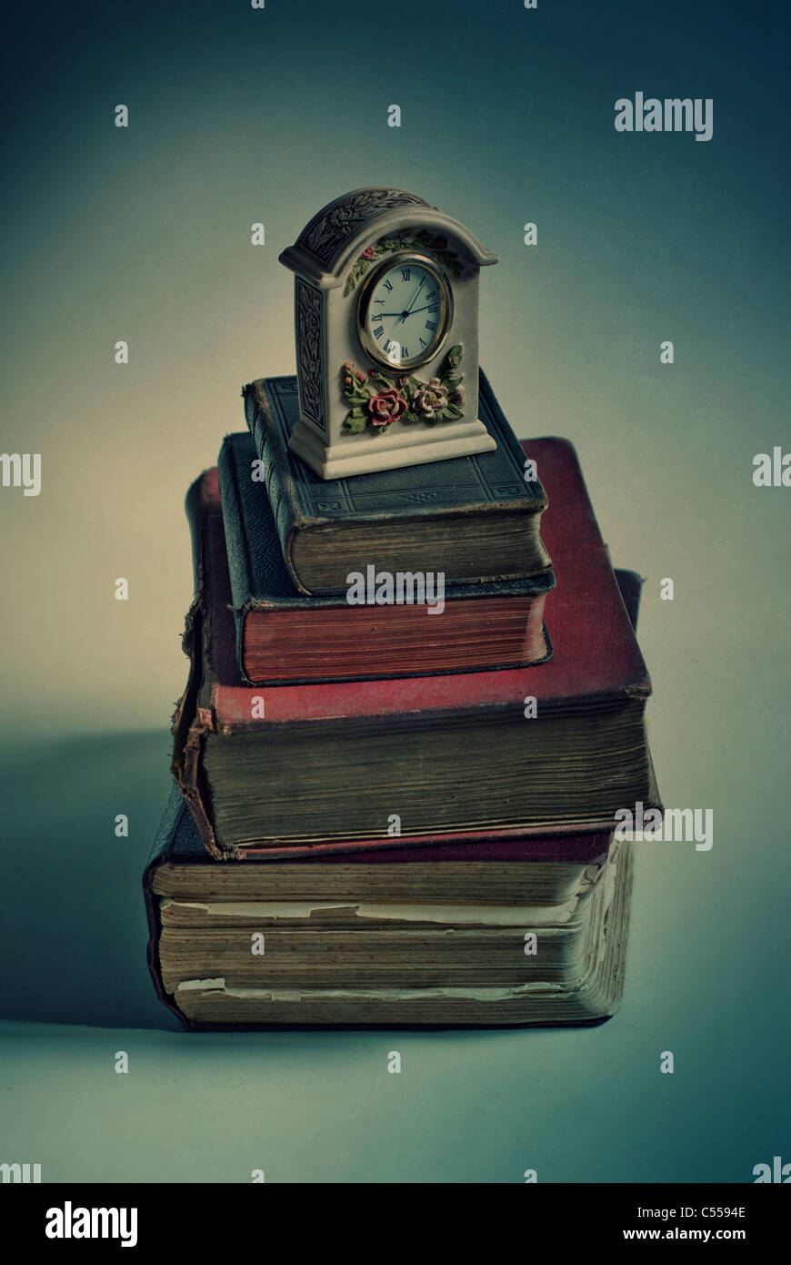 Old fashioned clock over a pile of books Stock Photo
