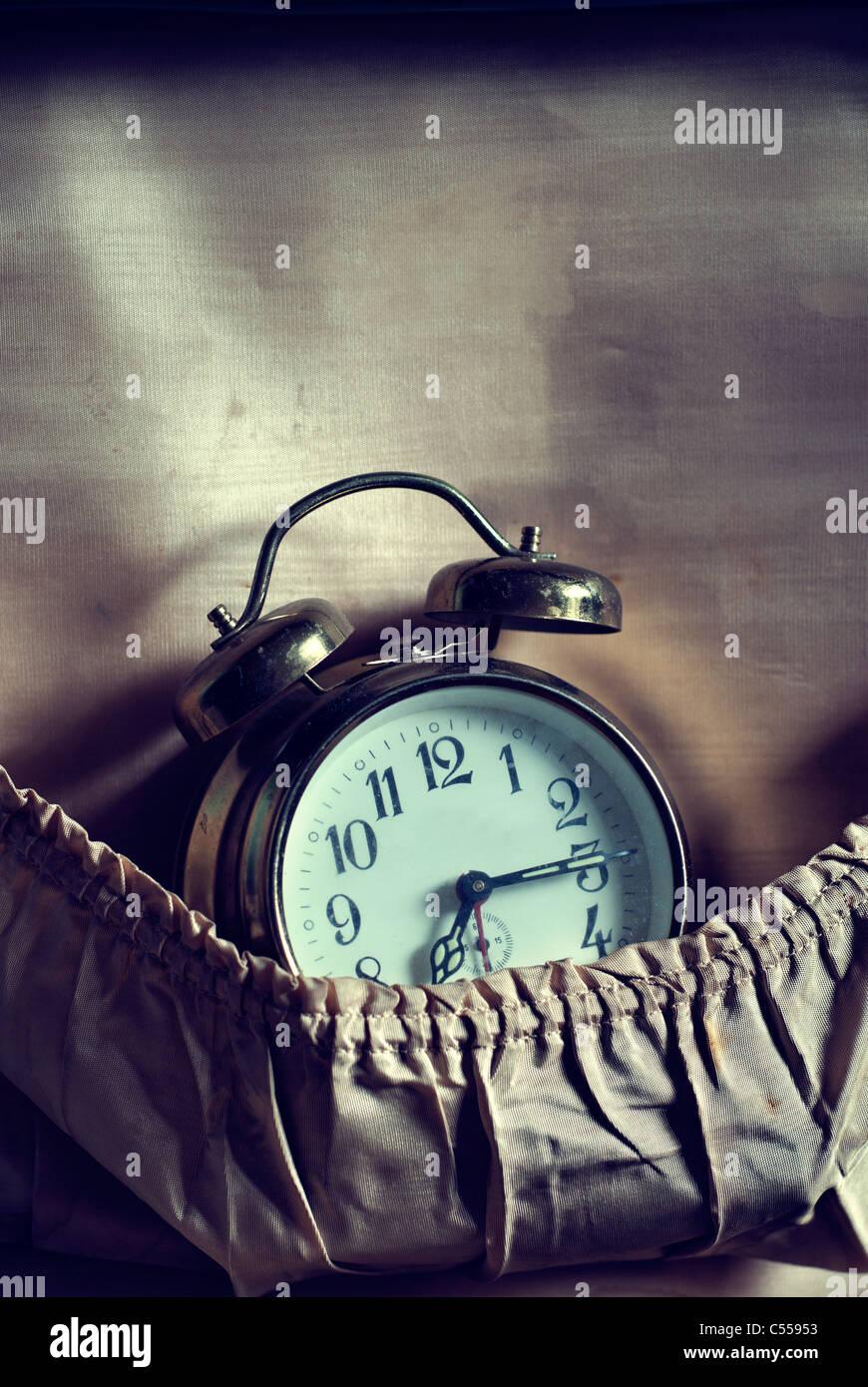 Vintage alarm clock in a suitcase pocket - Stock Image