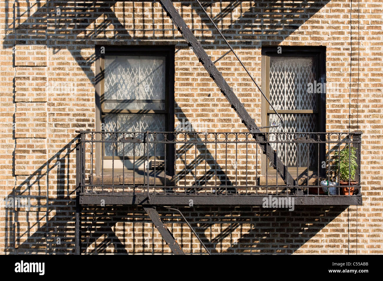 Brick Apartment Building With White Security Bars On The Windows And A Fire  Escape With Shadow