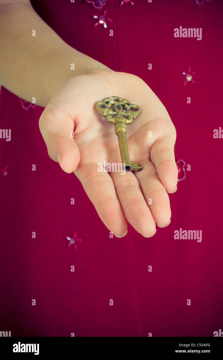 Woman holding an old key - Stock Image