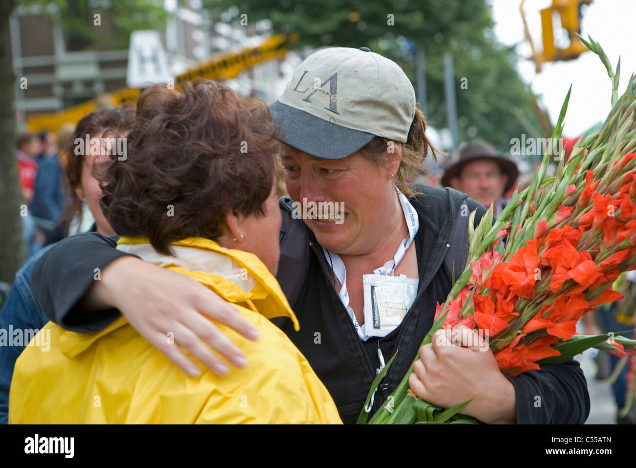 The Netherlands, Nijmegen. The Nijmegen Four-Day Walk. Supporter and participant with flowers at finish. - Stock Image