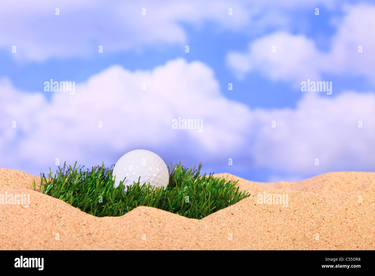 Golf concept photo of a ball lying on a patch of grass in a bunker. - Stock Image