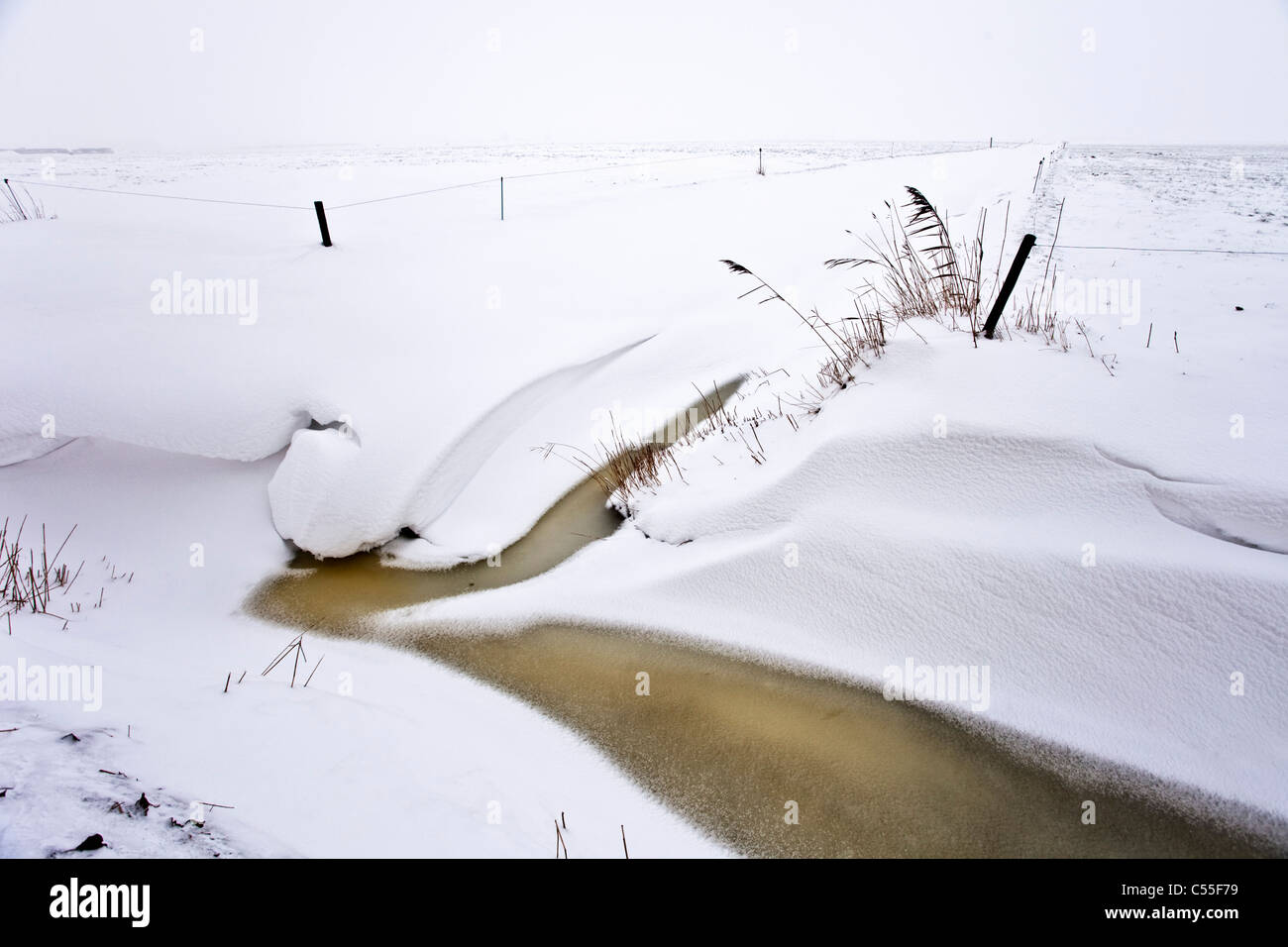 The Netherlands, Uithuizen, Snow in canal - Stock Image