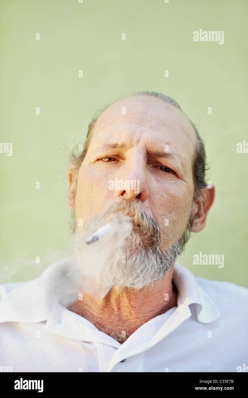 portrait of mature white man looking at camera against green wall with cigarette in mouth. Copy space - Stock Image