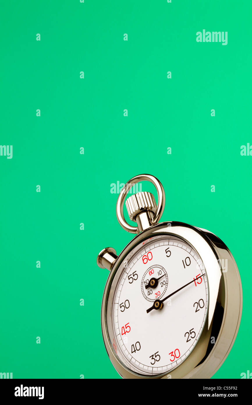 Stopwatch against green background - Stock Image