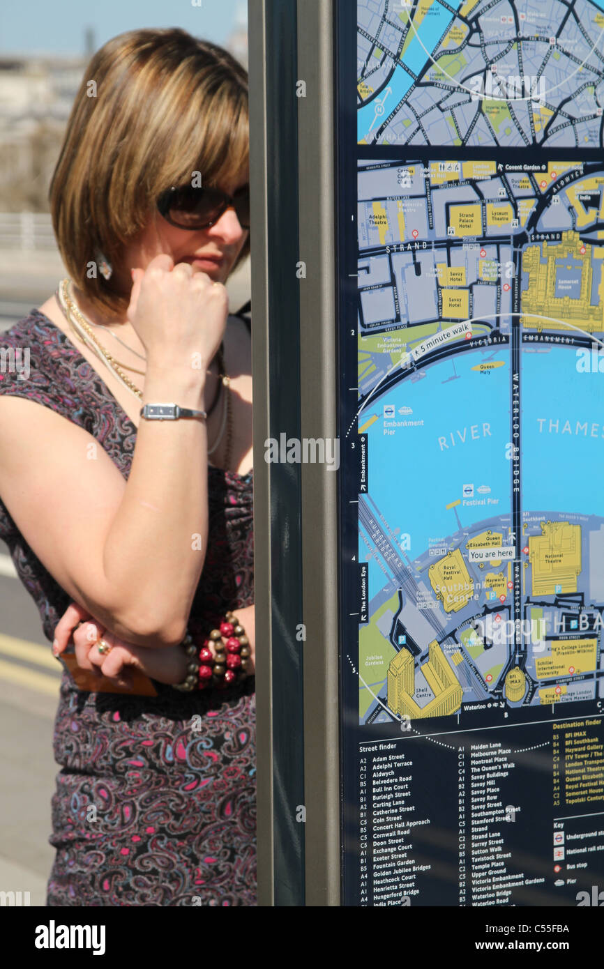 Woman tourist looking at a map of London by the river Thames. UK - Stock Image