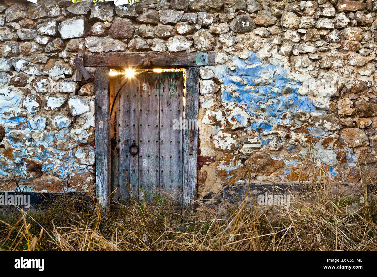 The Netherlands, Epen, Sun shining through door of run-down house. - Stock Image