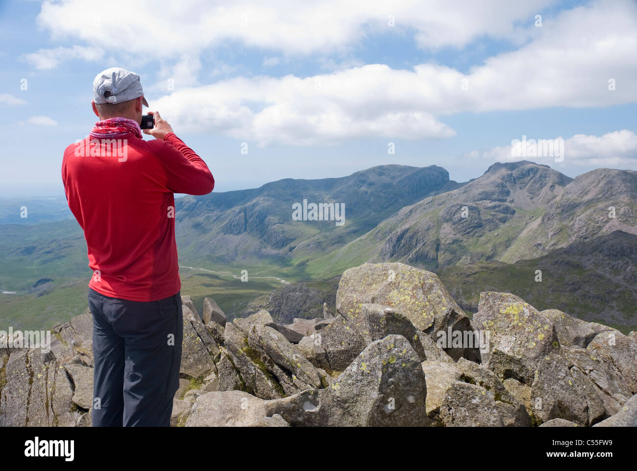 Walker taking a picture of the Scafell Range from Bowfell, Lake District, Cumbria. - Stock Image