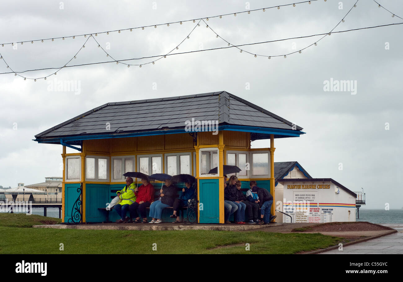 traditional British seaside holiday,People sheltering from summer rain in seaside shelter in Paignton,Devon,staycation,vacation - Stock Image