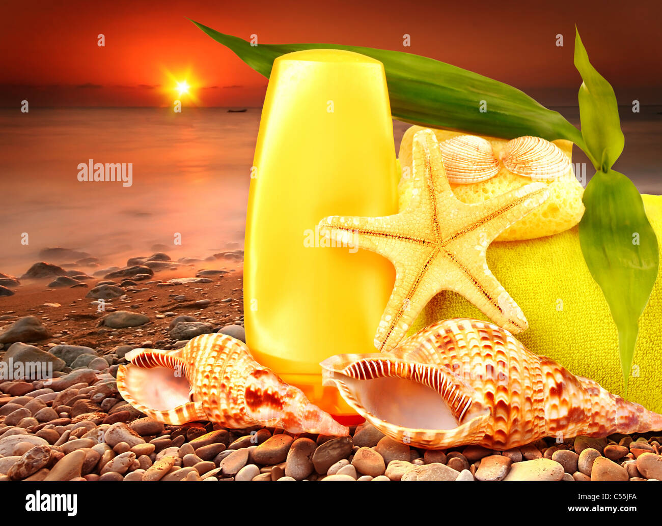 Beach items over sea sunset conceptual image of summertime vacation & holidays - Stock Image