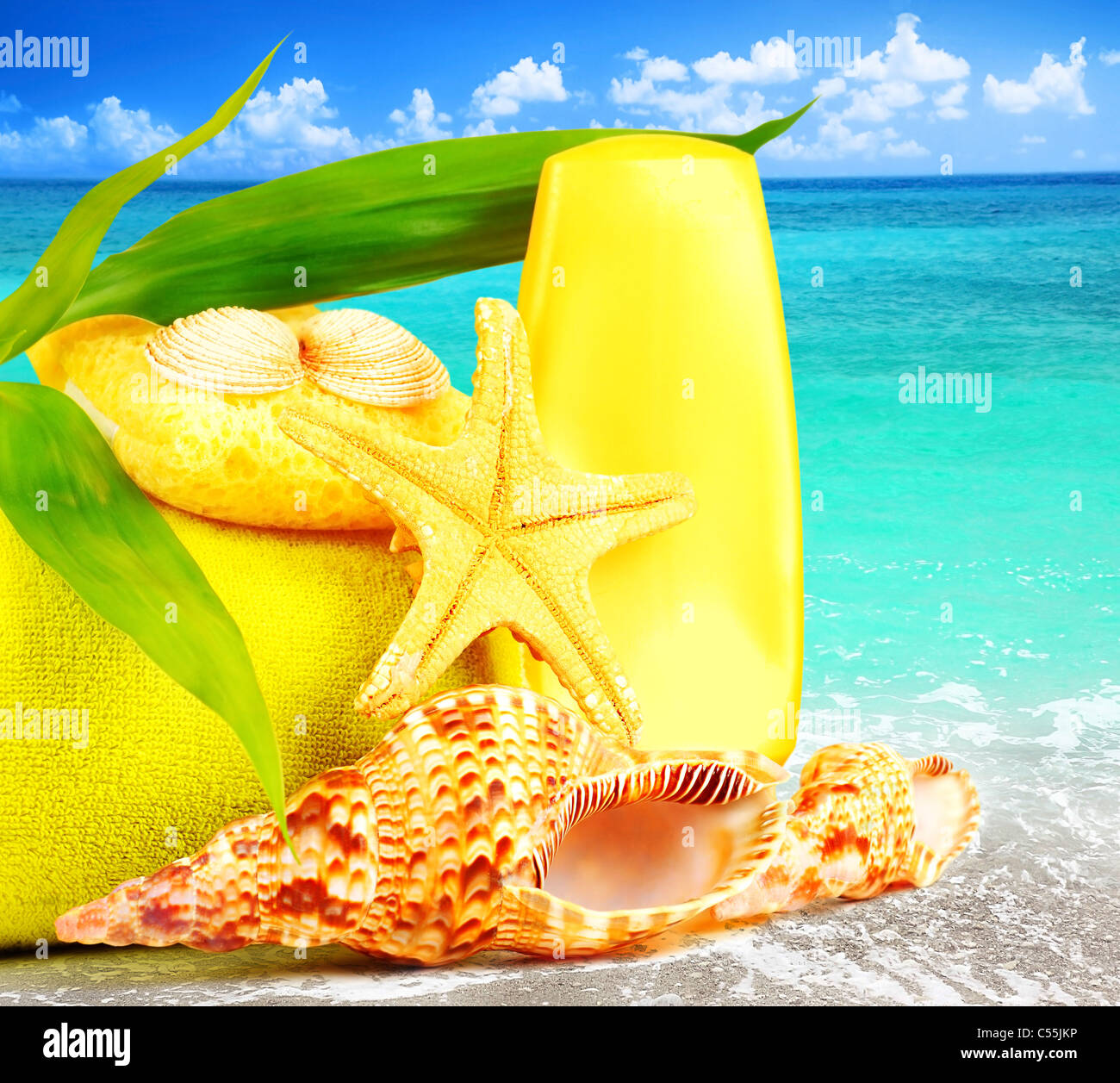 Beach items over blue sea conceptual image of summertime vacation & holidays - Stock Image