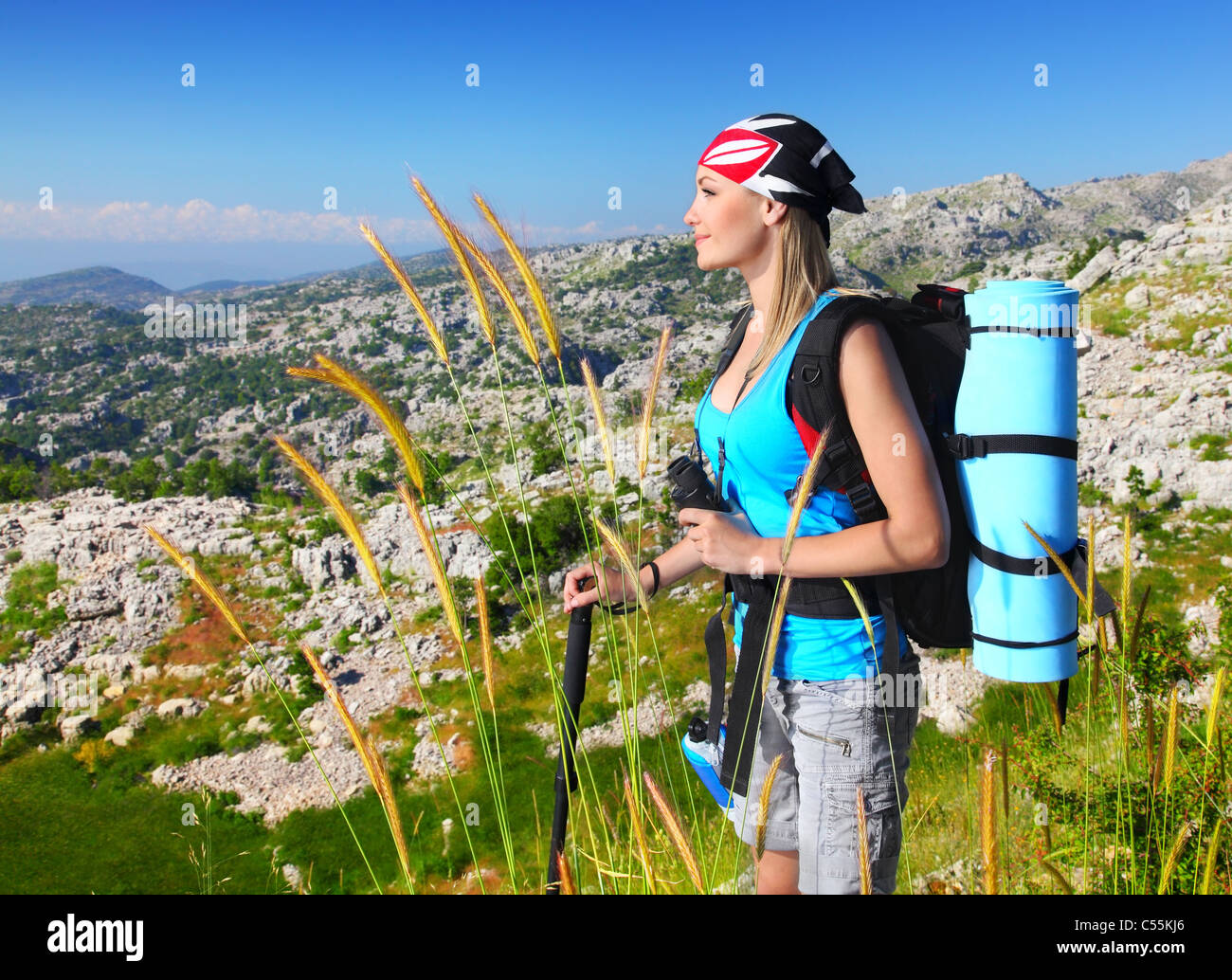 Traveling girl with backpack hiking in the mountains, eco tourism, freedom concept - Stock Image