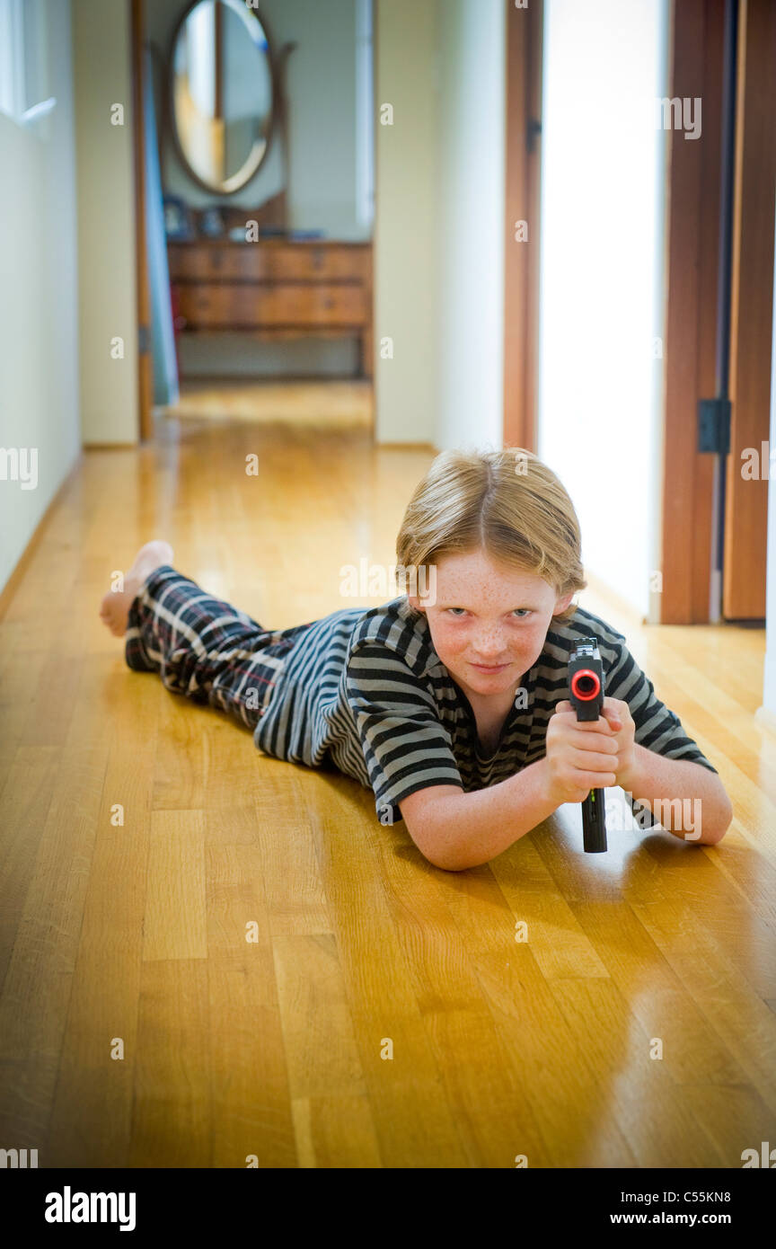 Boy playing with a toy gun - Stock Image