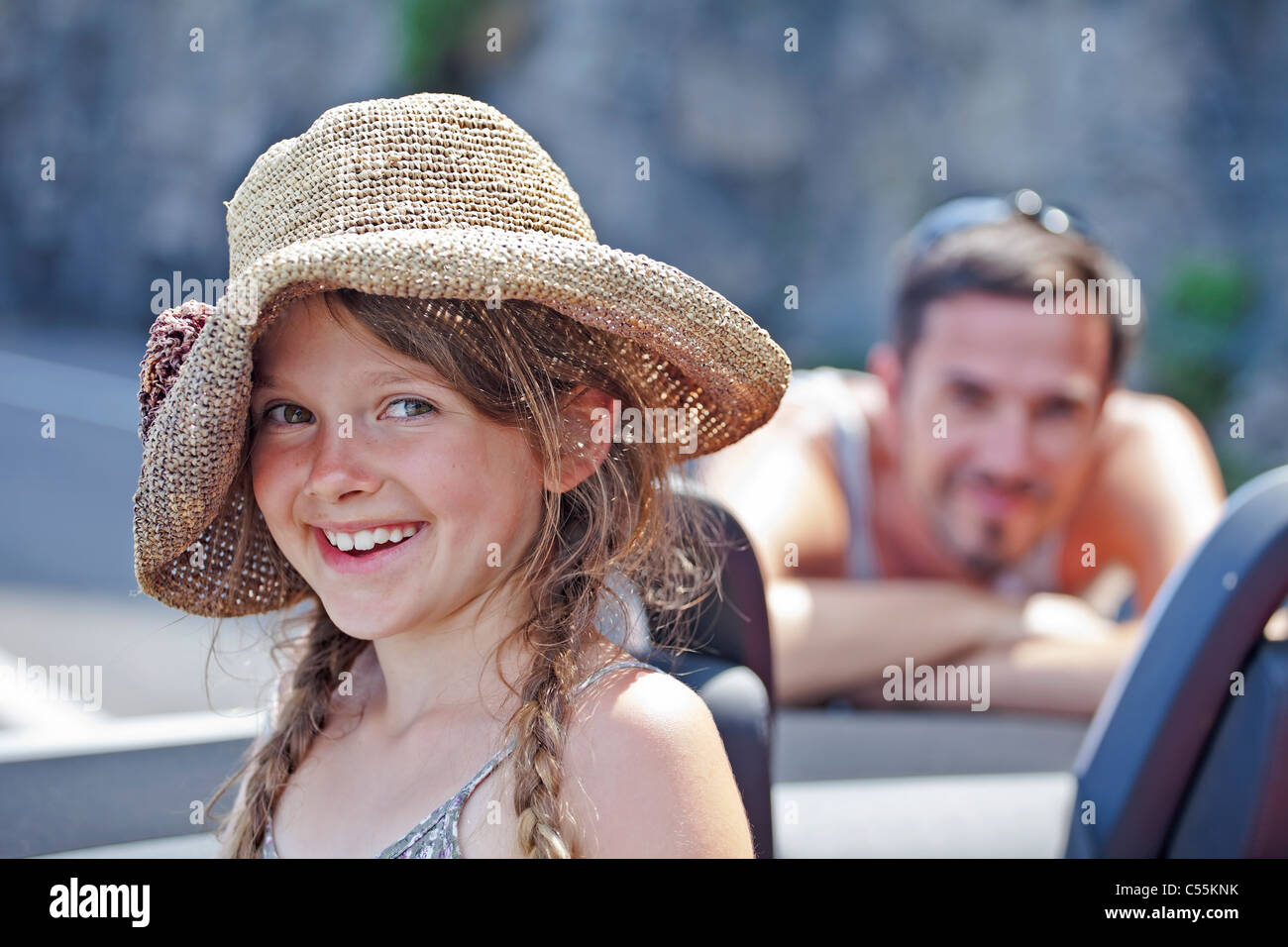 a seven-year-old girl in an open convertible in the summer - Stock Image
