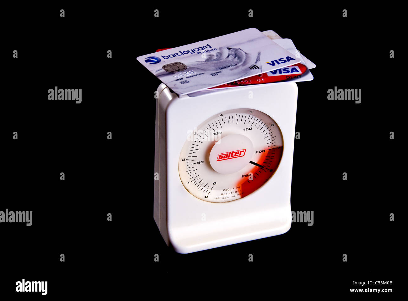 Credit cards on scales, heavy with debt going into the red. - Stock Image
