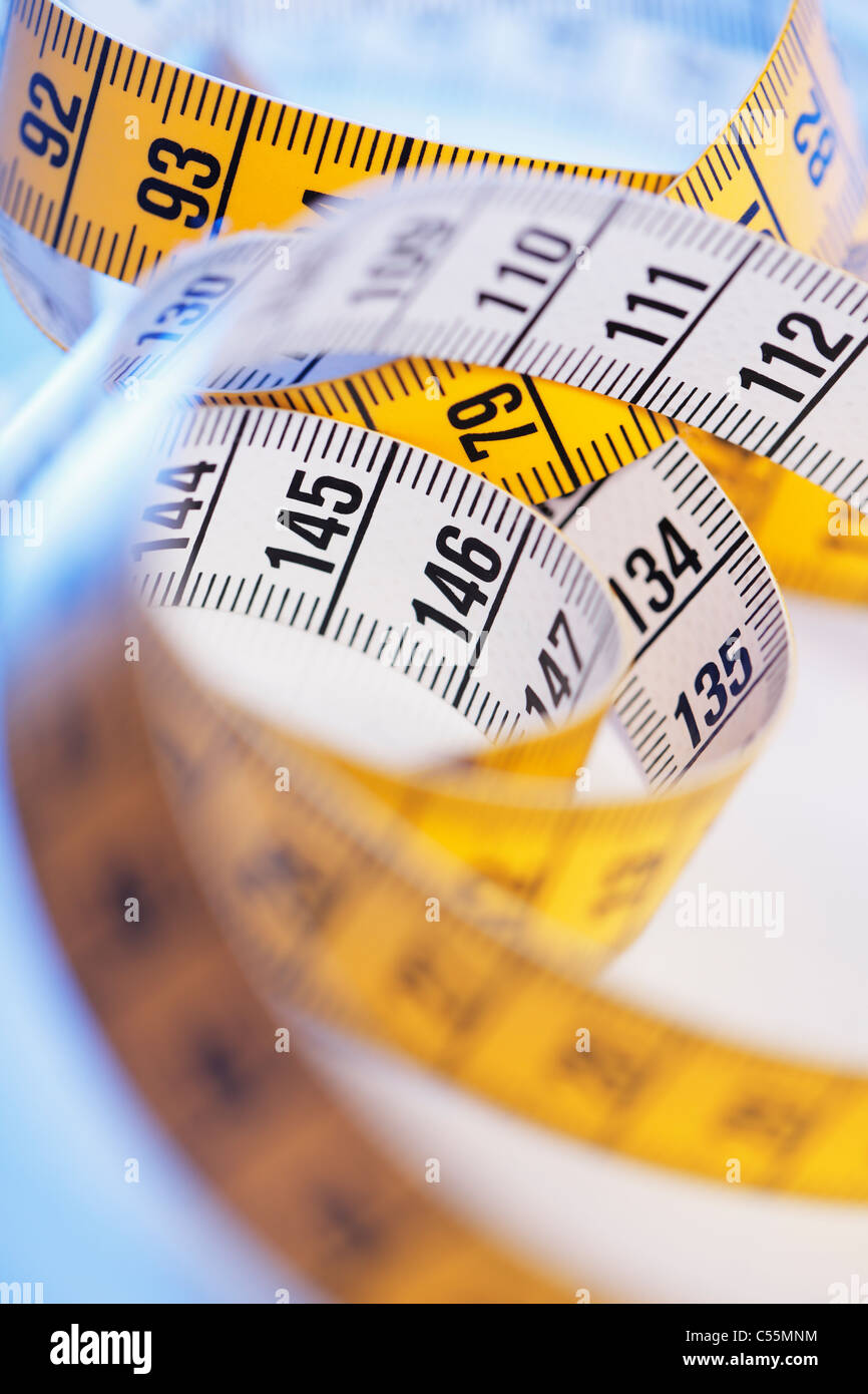 A Yellow and white metric tape measure in closeup. - Stock Image