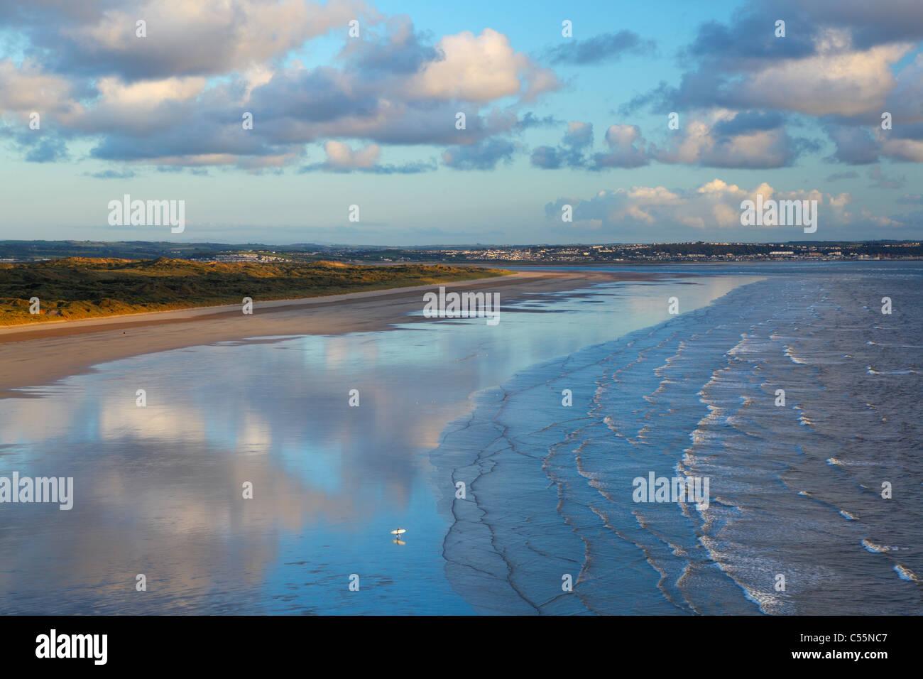 Lone Surfer at Saunton Sands with Braunton Burrows behind. Devon. England. UK. - Stock Image
