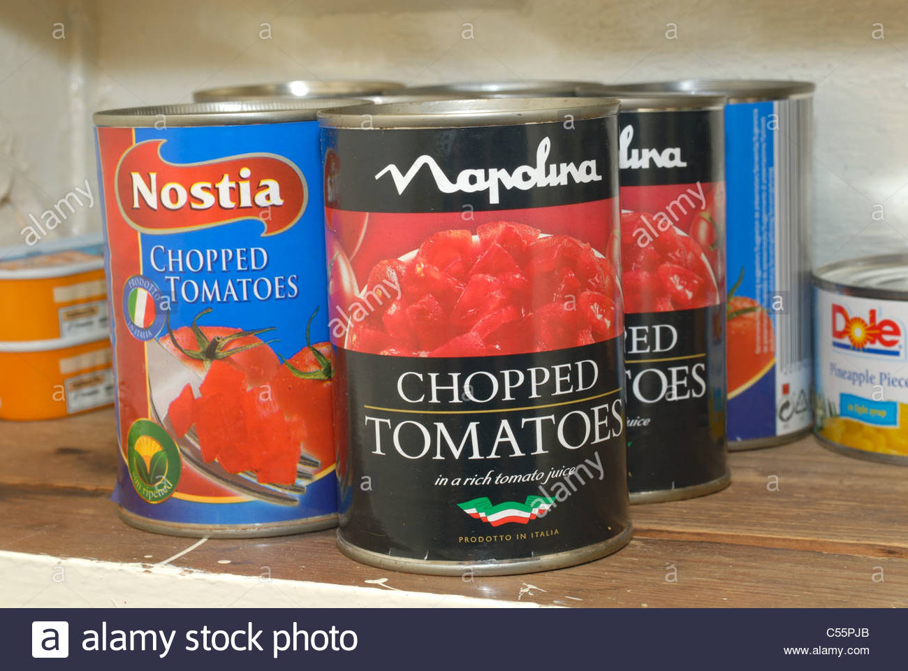 Tins of chopped tomatoes in a suburban larder. - Stock Image