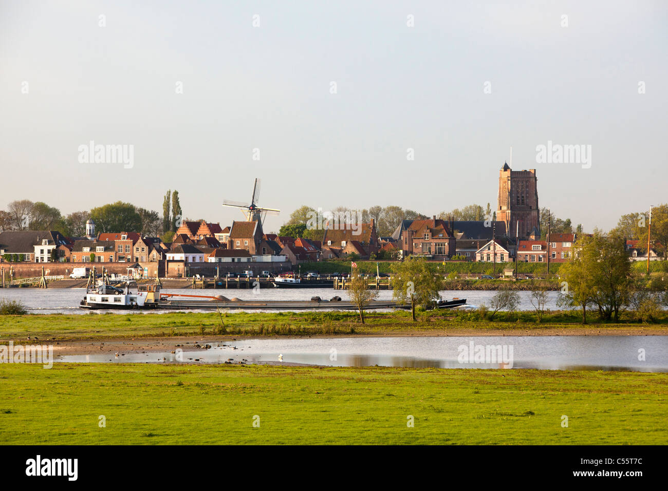 The Netherlands, Woudrichem, Skyline and cargo ship in river called Maas. Stock Photo