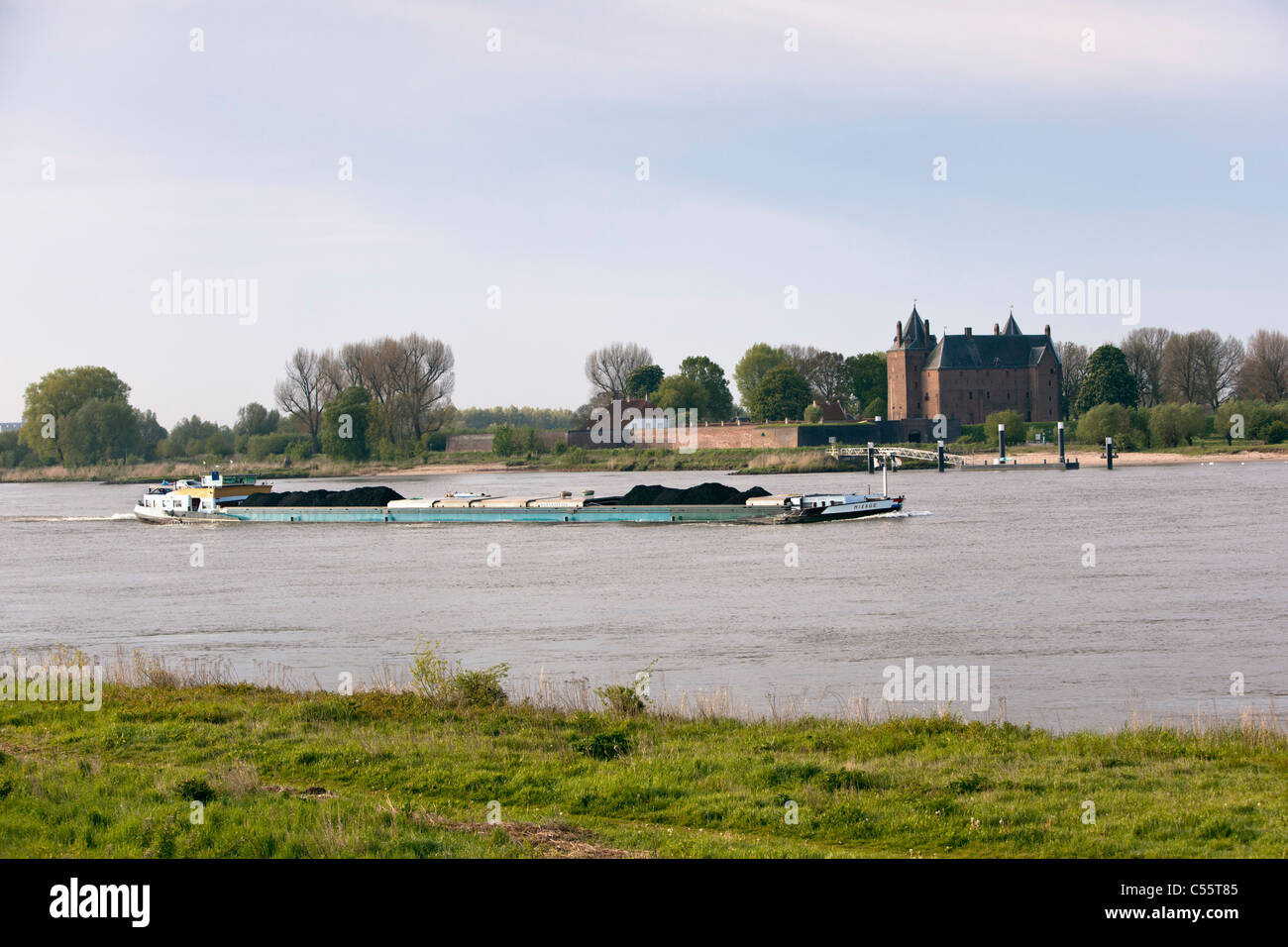 The Netherlands, Woudrichem, Loevestein Castle and cargo ship in river called Maas. Stock Photo