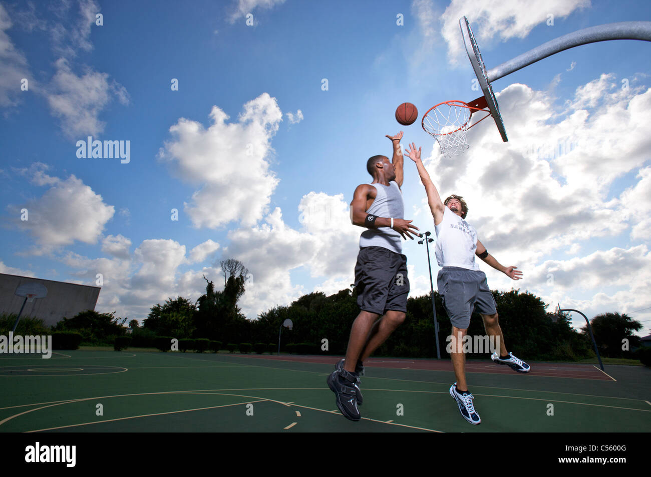 male scoring during outdoor basketball game of two on two - Stock Image