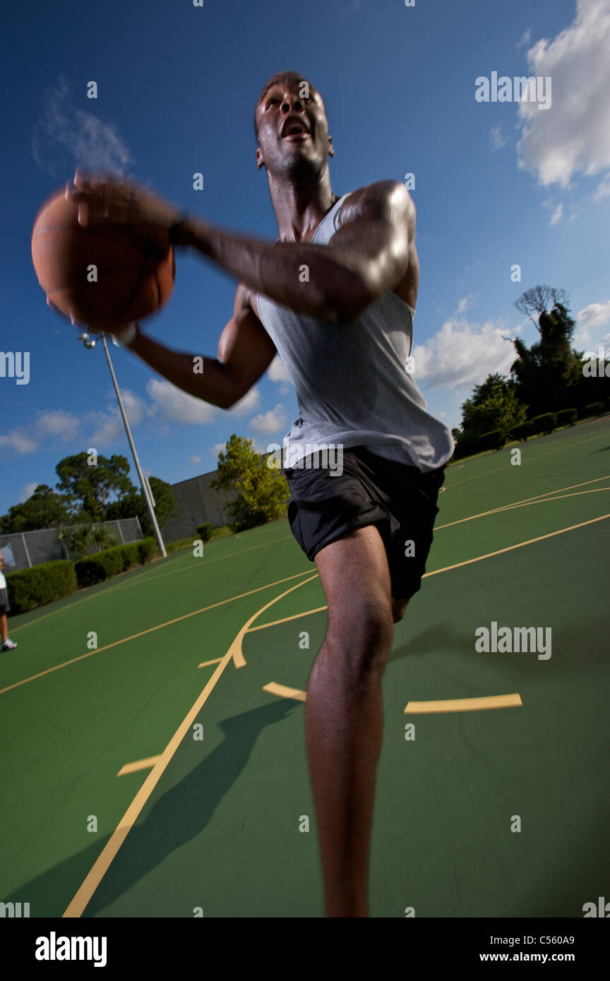 male driving during outdoor basketball game - Stock Image