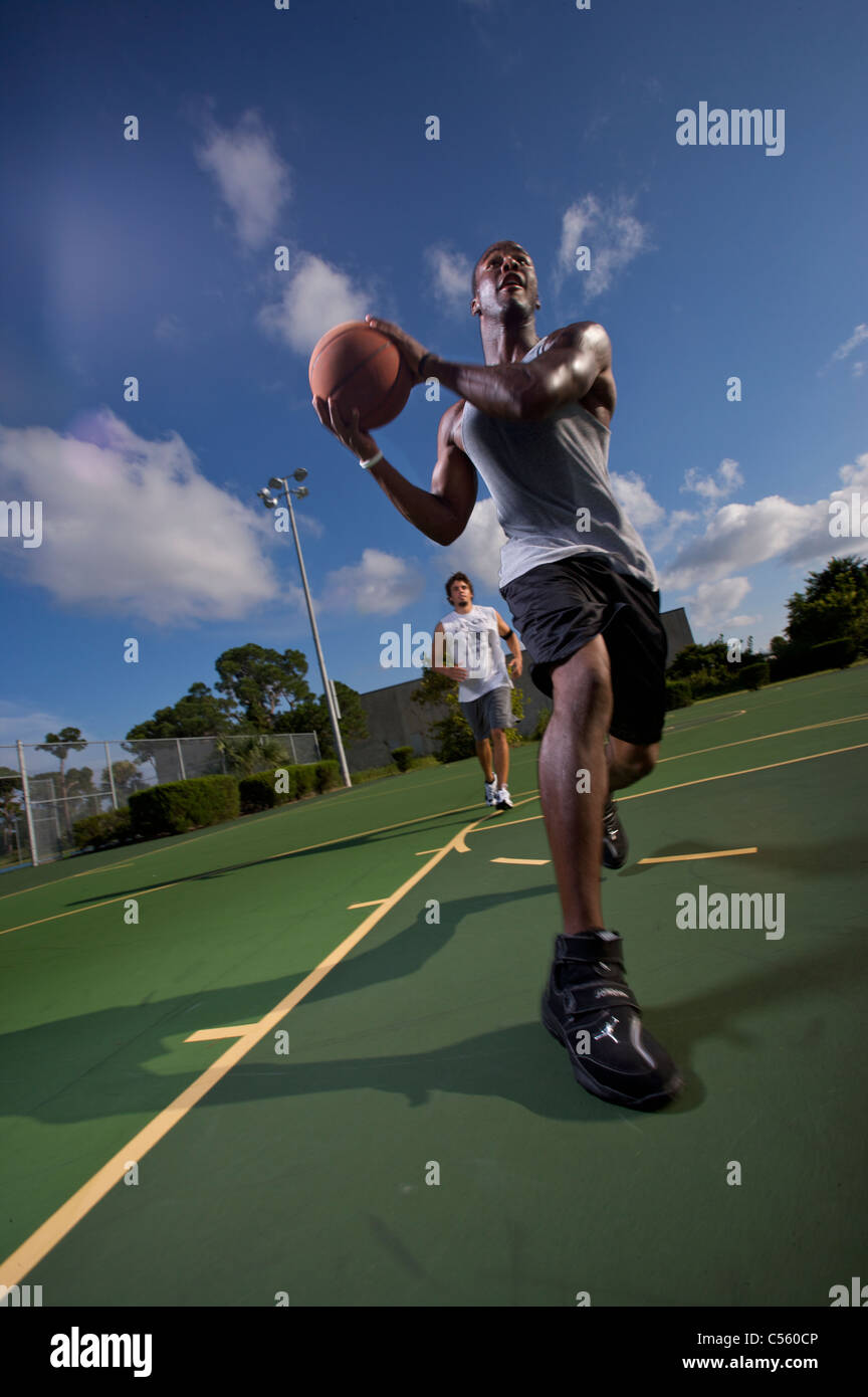 males playing outdoor basketball game, one driving to basket - Stock Image