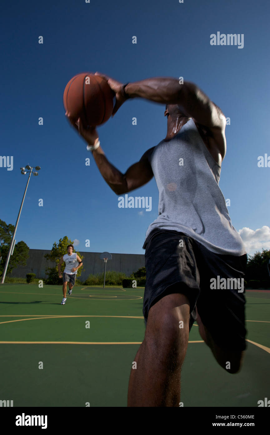 males playing outdoor street basketball with one player driving to basket - Stock Image
