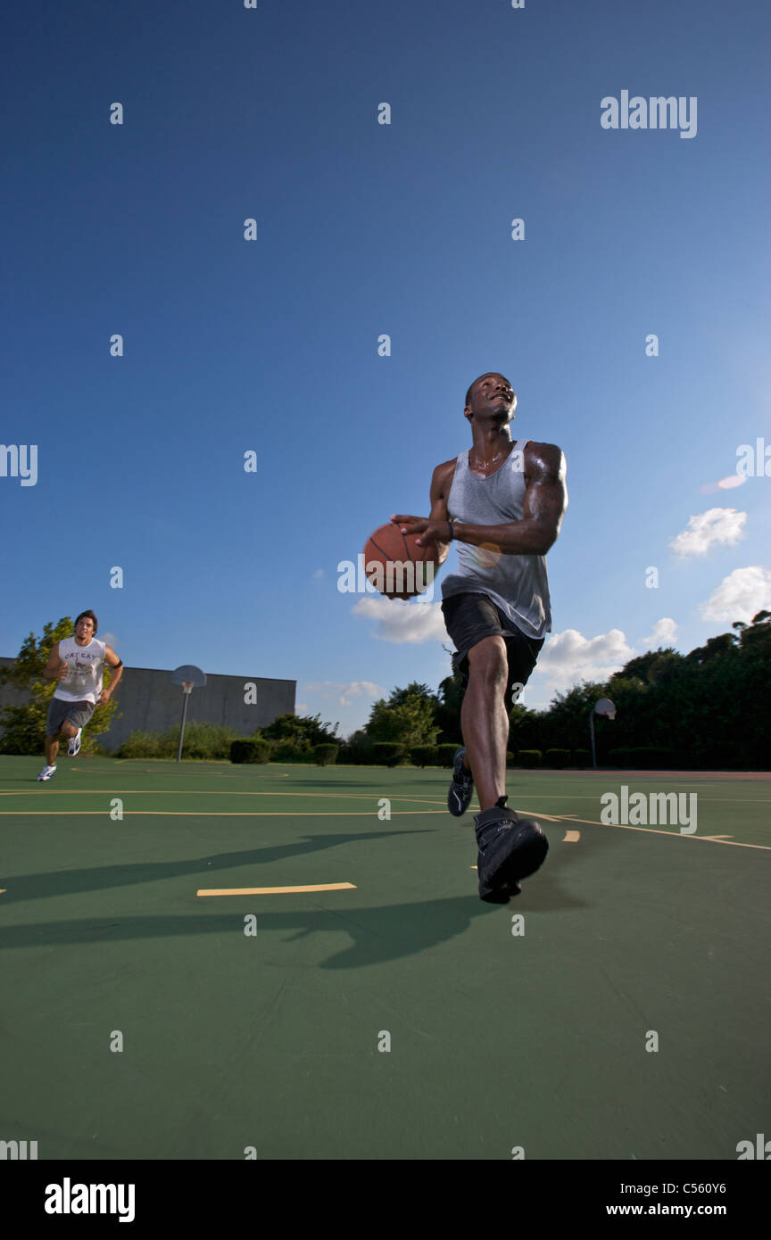 males playing outdoor street basketball with one driving to basket - Stock Image