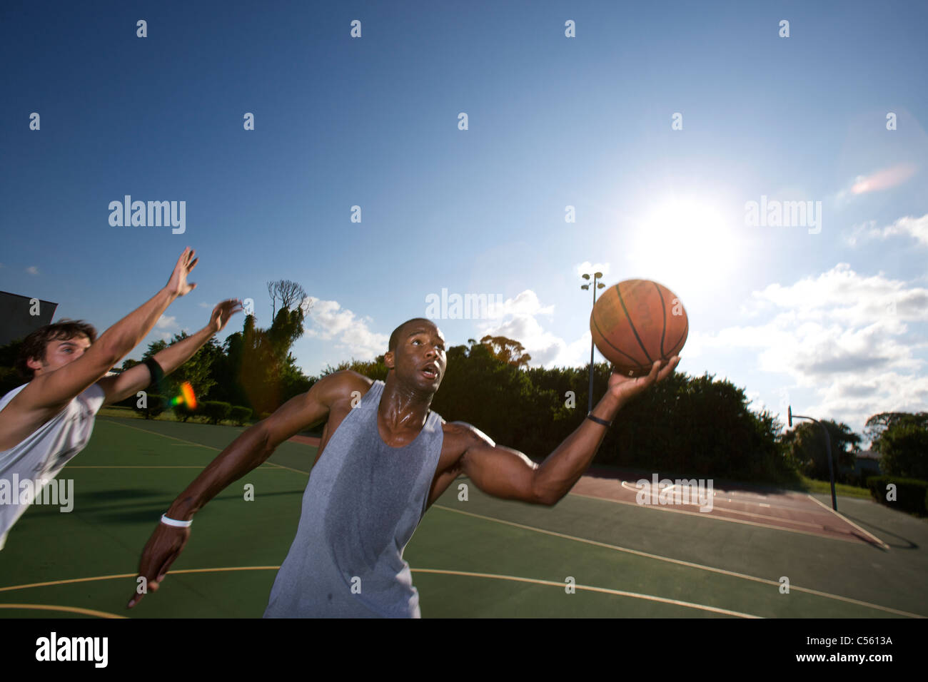 males playing outdoor basketball game - Stock Image