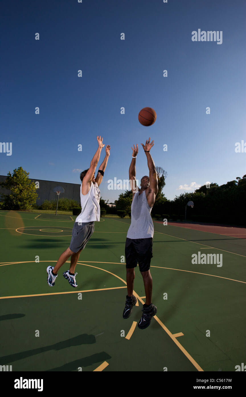 jump shot during two on two basketball game being defended - Stock Image