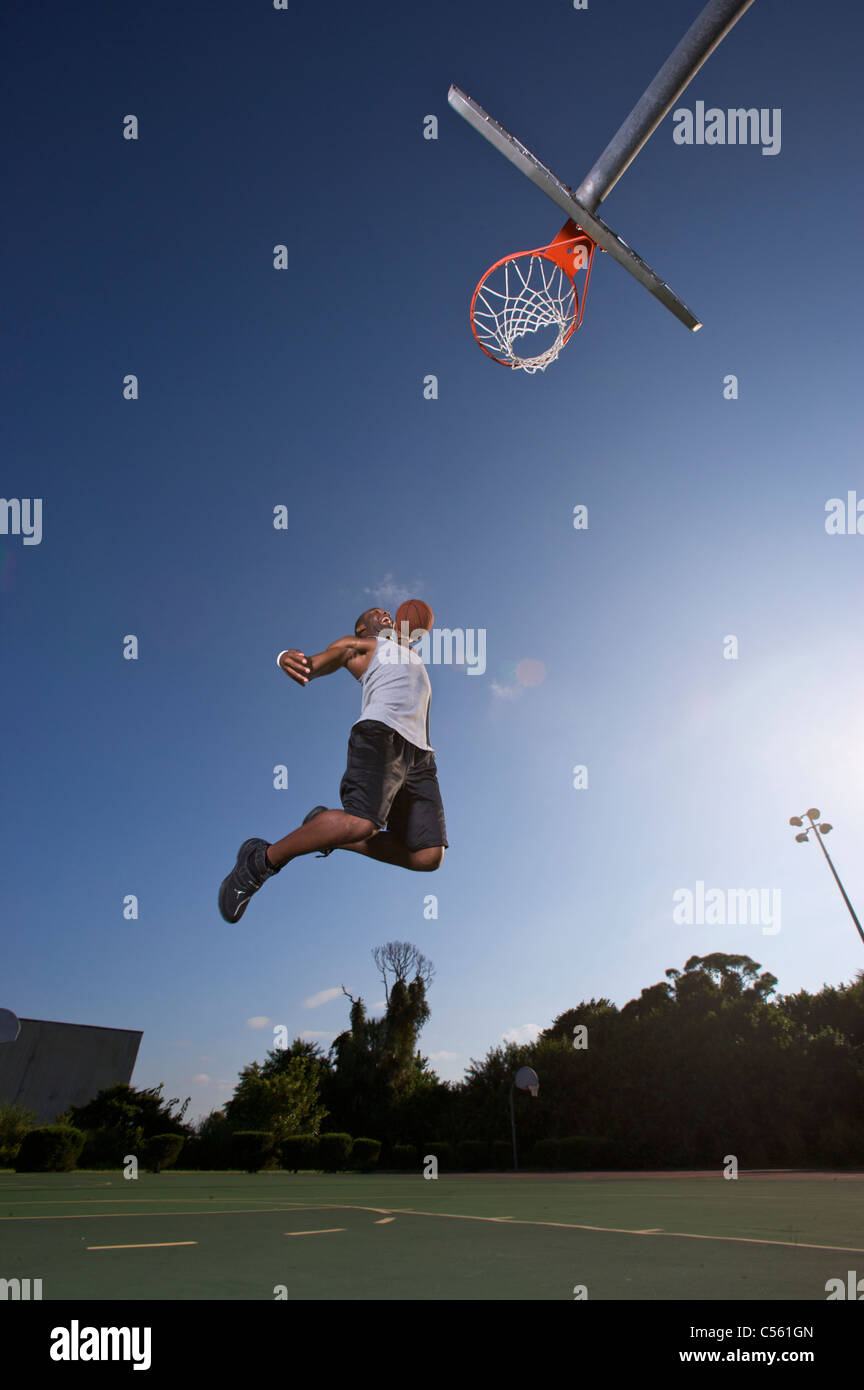 male making slam dunk during outdoor basketball game - Stock Image