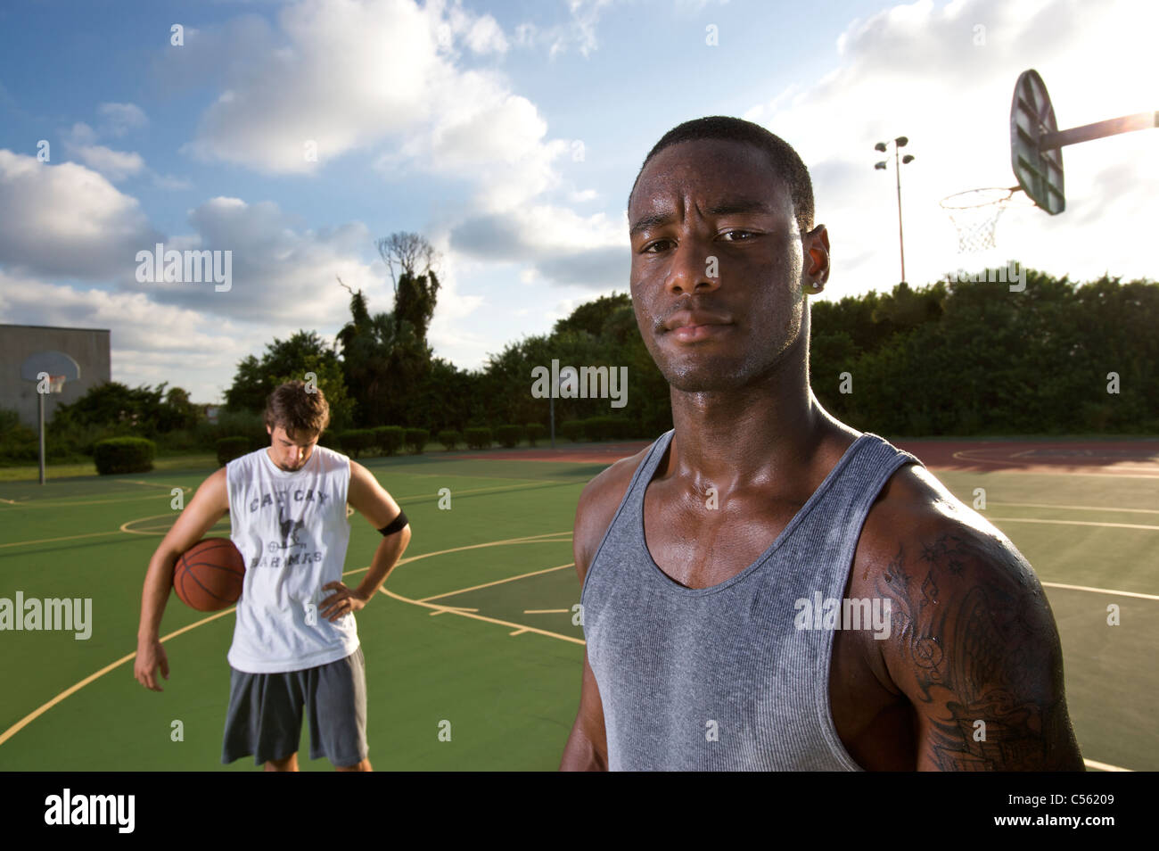 young males on outdoor basketball court - Stock Image