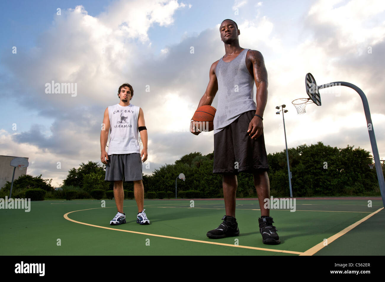 males after after playing basketball on outdoor court, dramatic sky - Stock Image