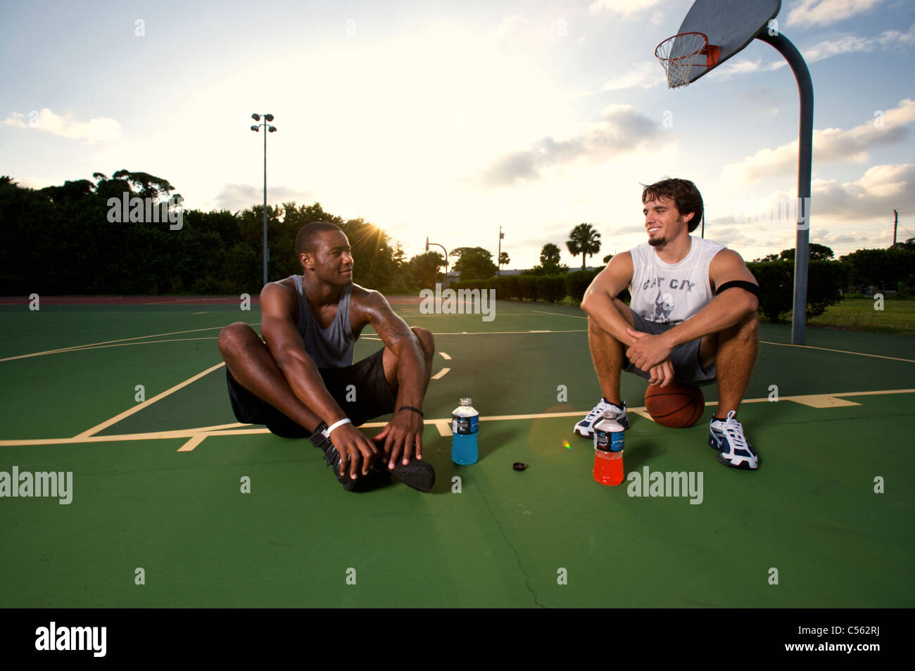 males resting, relaxing after after playing basketball on outdoor court, dramatic sky - Stock Image