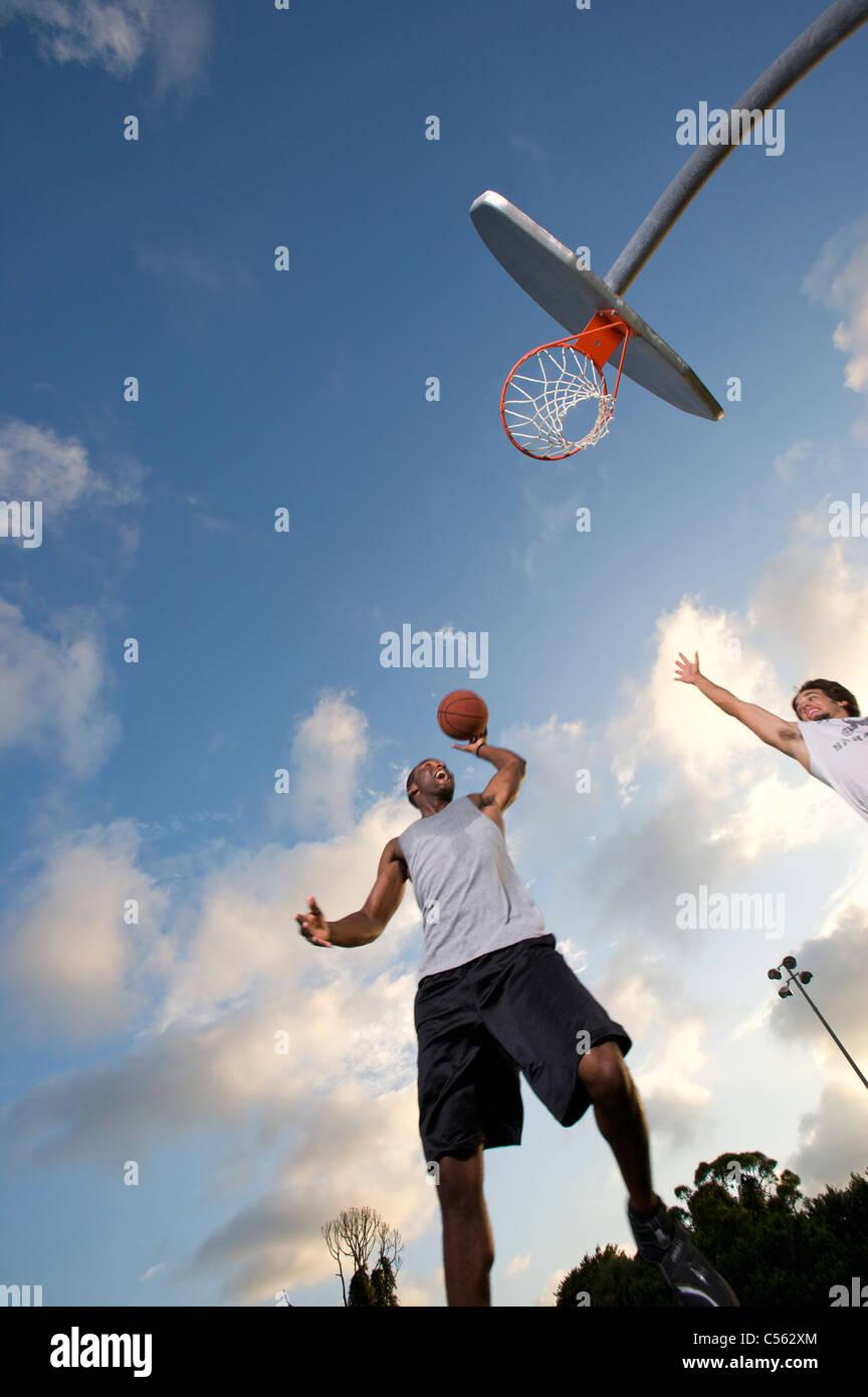 male scoring during outdoor basketball game, looking upward toward goal - Stock Image