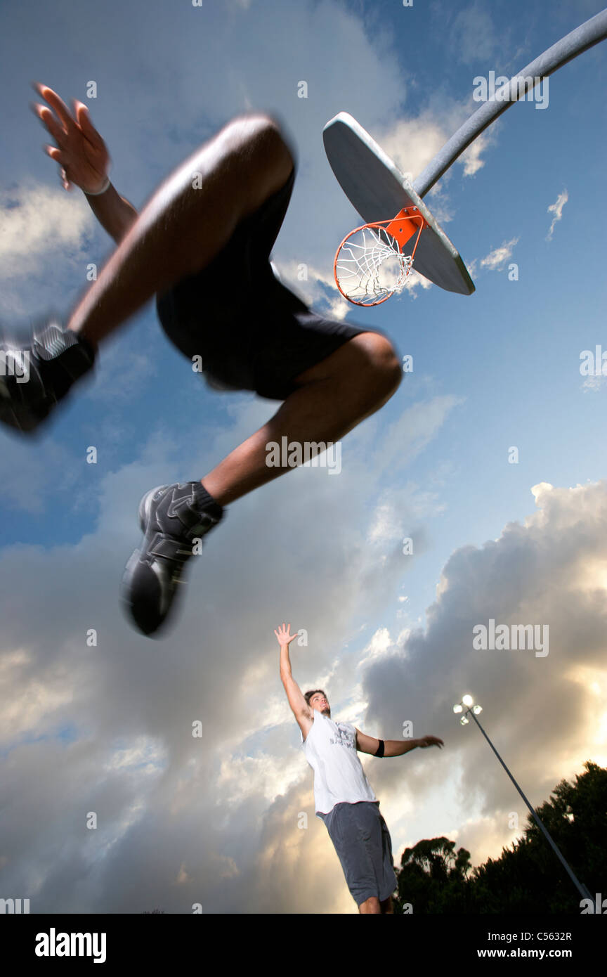 male scoring during outdoor basketball game, viewed from below - Stock Image