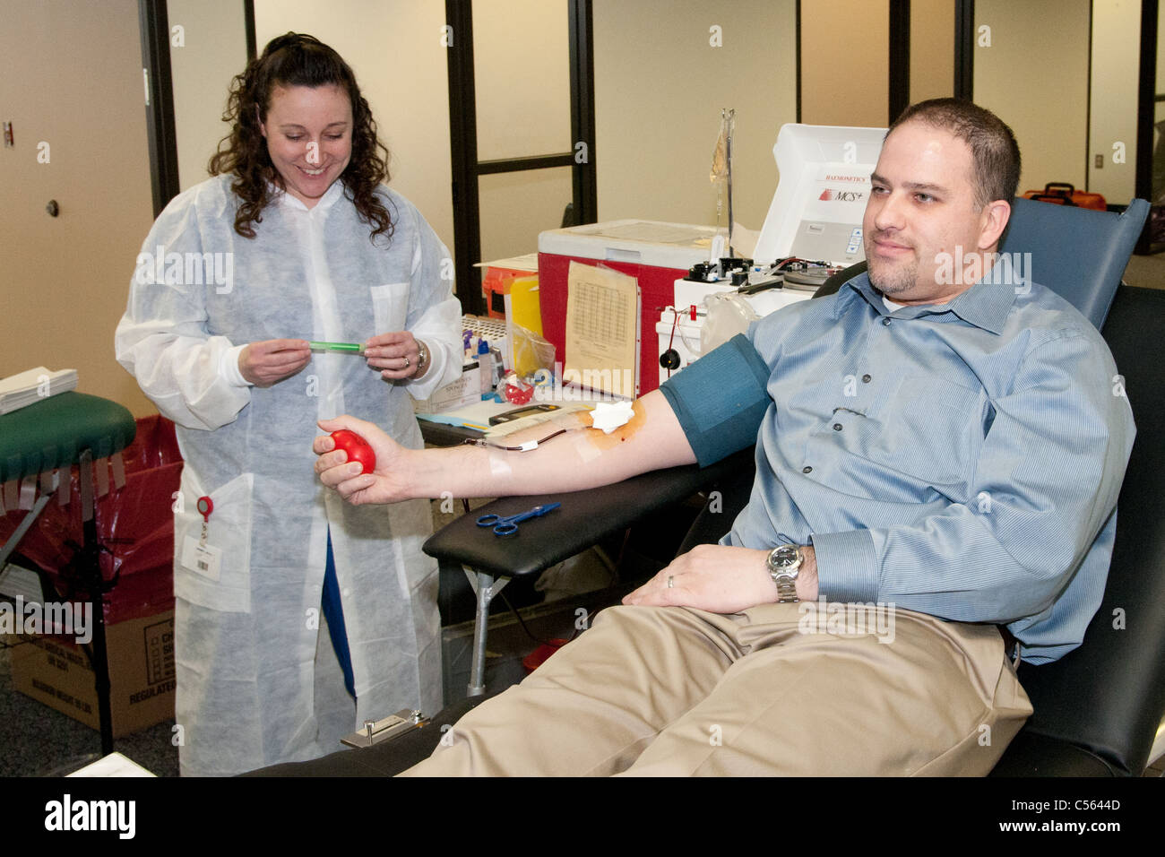 Man donates blood during a Red Cross Blood Drive at an office park - Stock Image