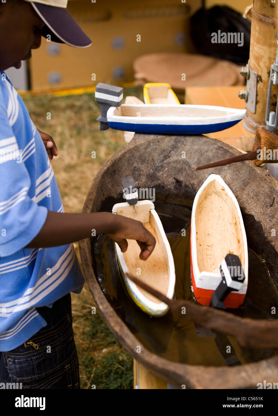 Young African boy inspects toy wooden boats in tub of water Stock ...