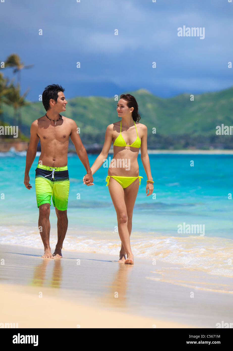 couple at the beach walking along the water's edge - Stock Image