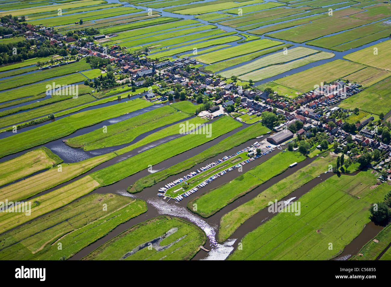 Netherlands, Wormer, Polder with village and farmland and mooring place with small boats. Aerial. - Stock Image
