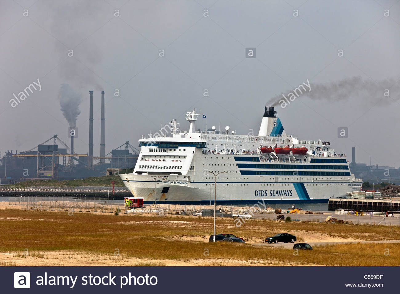 The Netherlands, IJmuiden, DFDS ferry to Newcastle leaving for the Norh Sea. Background Tata Steel blast furnaces. - Stock Image