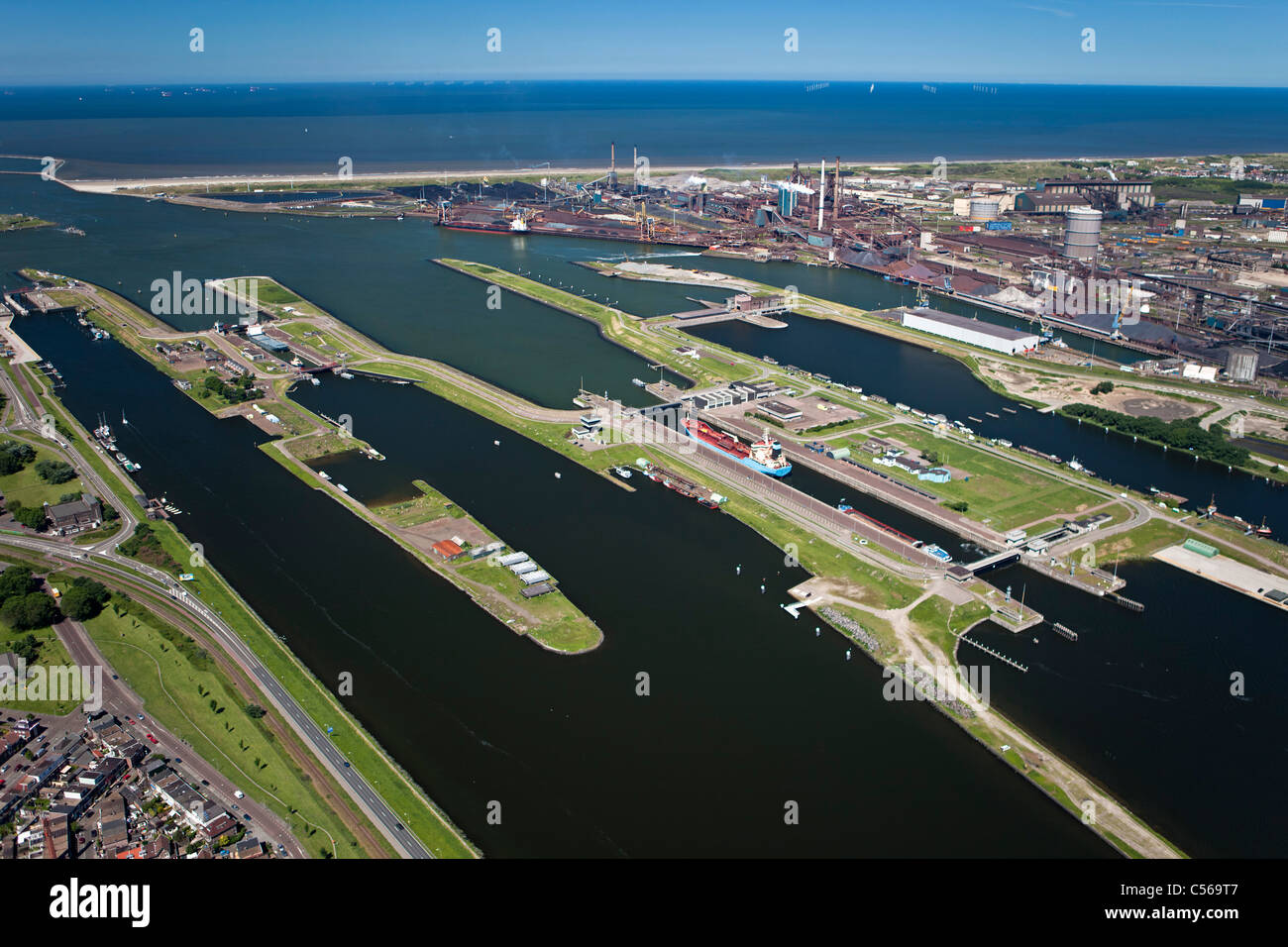 The Netherlands, IJmuiden, Aerial view of entrance and locks of North Sea Canal. Right Tata steel factory. - Stock Image